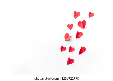 Flying red paper hearts on white background. Valentine's Day. Symbol of love. Copy space. Copy space. close up minimalism top view