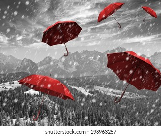 Flying red umbrellas in the mountains during a storm.