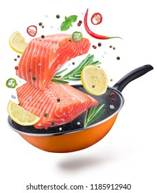 Flying salmon steaks and spices over a frying pan. File contains clipping path. Flying motion effect.
