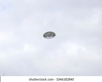Flying saucer UFO hovering in cloudy sky, reflective metallic body reflecting houses, CGI recreation