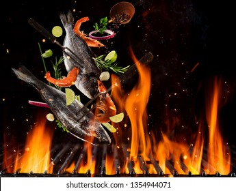 Flying sea breams and prawns above burning grill grid, isolated on black backround. Barbecue and grill concept