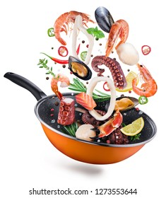 Flying seafood with spices falling into a frying pan. Flying motion effect of cooking process.
