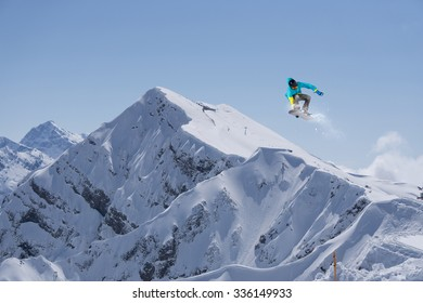 Flying snowboarder on mountains, winter extreme sport