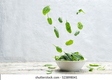 flying spinach on a wood background. tinting. selective focus