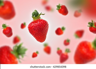 Flying strawberries on pink background