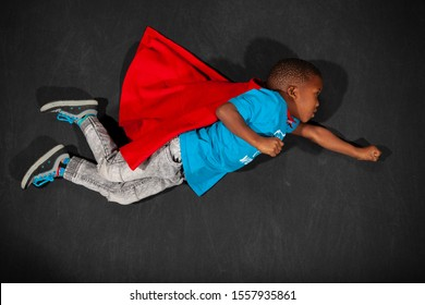 Flying super hero boy with red cape
