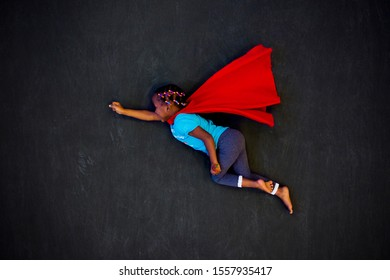 Flying super hero girl with red cape