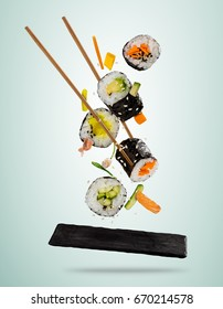 Flying sushi pieces served on stone plate, separated on soft background. Many kinds of popular sushi food with chopsticks. Very high resolution image
