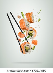 Flying sushi pieces served on plate, separated on colored background. Many kinds of popular sushi food with chopsticks. Very high resolution image