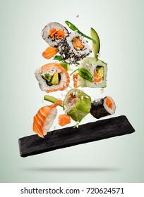 Flying sushi pieces served on stone plate, separated on soft background. Many kinds of popular sushi food. Very high resolution image