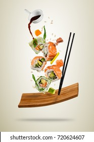 Flying sushi pieces served on wooden plate, separated on soft background. Many kinds of popular sushi food with chopsticks. Very high resolution image