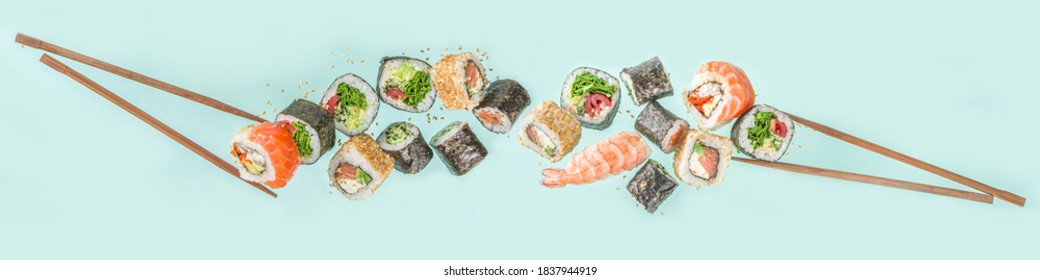 Flying sushi set with chopsticks. Various delicious japanese sushi, roll pieces and nigiri on light blue background