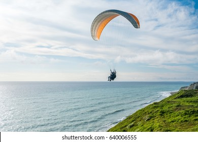 Flying tandem paragliders over the sea and near the mountains, beautiful landscape view