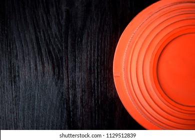 Flying target plate for shotgun sport against the dark wooden background. Copy space