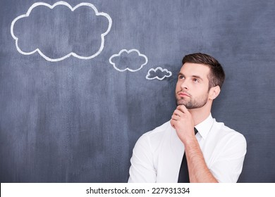 Flying of thoughts. Thoughtful young man holding hand on chin and looking away while standing against cloud chalk drawing on blackboard