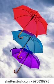 flying umbrellas in front of blue sky