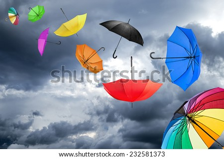 flying umbrellas in front of dark sky