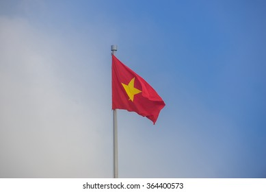 Flying Vietnamese flag isolated on a blue sky background in the bright sunny day