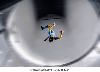 I flying in wind tunnel. New skydiving sport in flight technology. Indoor skydiving. Training in wind tunnel.