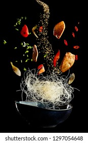 flying wok with chicken and spices. Concept of food preparation in low gravity mode, food levitation. Separated on black background. High resolution image