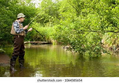 Flyrod fisherman fishing on a trout stream wearing waders