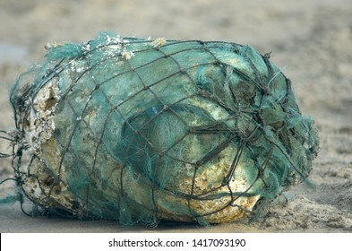 A foam buoy, originally white but stained from the sea, has been wrapped in green fishing net with black ties. It has been washed up onto a beach, and lies horizontally on the sand.