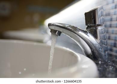 Foam like water stream  is fallen from a chrome metal tap to a white sink