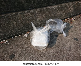 Foam packet in plastic garbage after used on the walkway roadside. The people throwing trash carelessly in anywhere not a bin. Environment negligently concept.