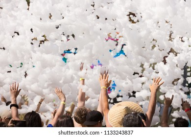 Foam party entertainment, people have fun raising hands catch soap bubbles, summer entertainment festival in aquapark, background or texture of white foam with copy space