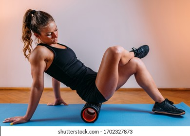 Foam Roller. Woman Using Foam Roller for Gluteus Muscle and Fascia Self Massage at Home