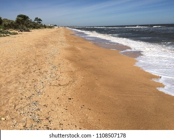 The foam of the sea and yellow sand.