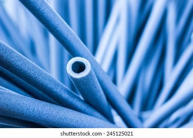 Foam tubes in the warehouse. In blue tones