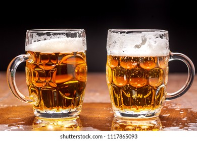 Foamed beer in a glass mug on a dark background.