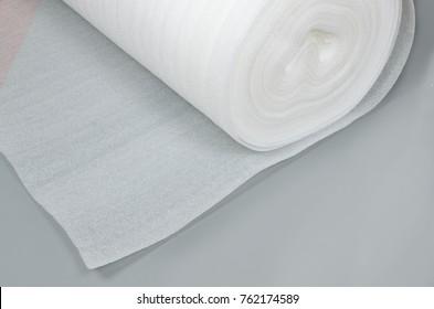 Foamed polyethylene in a roll on a gray background
