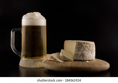 Foaming beer with artisanal goat cheese on wooden board