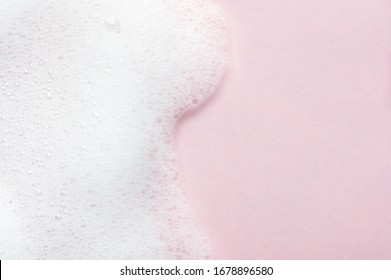 Foaming liquid on pink backdrop. Cosmetics foam background with copy space in right side. Cosmetic product sample of mousse, shampoo or soap. Skincare, cosmetology and beauty concept