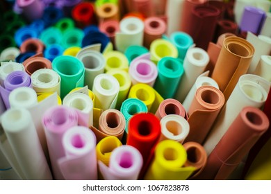 Foamiran sheets are rolled into rolls. Foamiran is a decorative foamy material for creating artificial handmade flowers. The concept of women's hobbies and business. View from above.