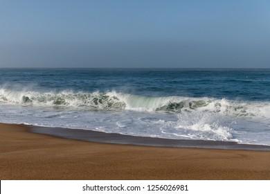 Foamy Atlantic ocean wave on Nazare city beach, Portugal.