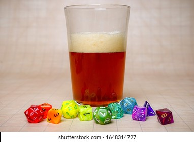Foamy beer alcohol drink in pint glass. Rainbow roleplaying Dungeons and Dragons DND dice for game night on grid mat. Represent LGBT (Lesbian, Gay, Bisexual, Transgender) community in board games.