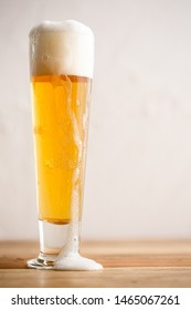 Foamy, freshly poured golden pilsner in cold beer glass against white background spilling slightly into foreground