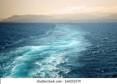 Schaumspur hinter dem Heck des Schiffes über der Küste