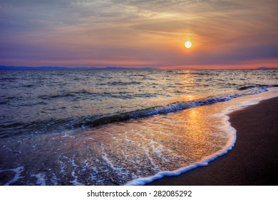 Foamy water crashing onto sandy beach shore at sunset with distant cliffs