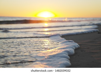 Foamy wave on sand at beach during sunrise