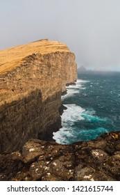 Foamy waves of blue sea crashing near rough stony cliff against gray sky on Faroe Islands