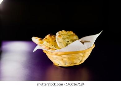 Focaccia in the basket. Focaccia on a dark background.
