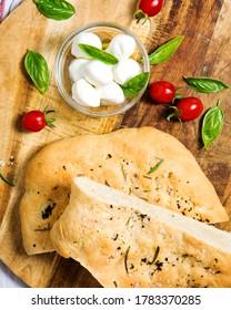 focaccia bread with mozzarella di buffola an tomatoes on a wooden plate