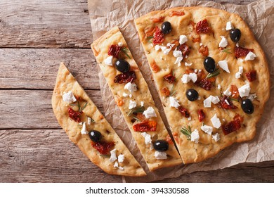 Focaccia with dried tomatoes, feta and olives on the table. horizontal view from above