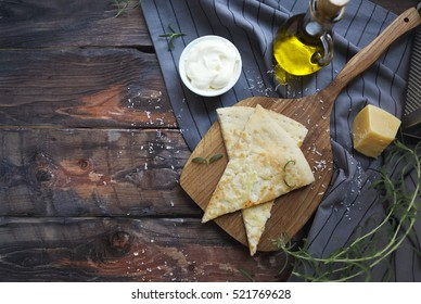 Focaccia with olive oil, parmesan cheese, white sause and rosemary. Homemade traditional Italian bread focaccia on the linen napkin.