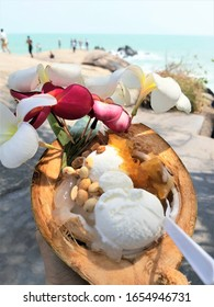 Focal focus at the mid section, blurred in the front and back of the picture. The picture of beach coconut ice cream decorated with hibiscus flowers, condiments peanuts, dried pineapples, palm candy.