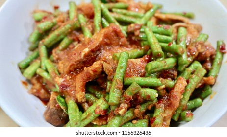 Focal focus of Thai dish stir fried pork  belly with red curry paste and sting beans, tasty and spicy famous icon. Meat can be seafood, pork, chicken, beef depends on the order and favor